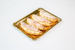 Gebakjes in een gouden dienblad op witte achtergrond royalty-vrije stock foto's