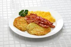 Gebakken aardappelen, roereieren en bacon stock foto's