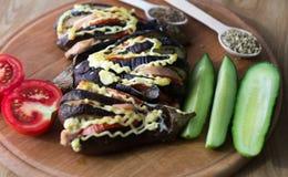 Gebakken aubergines, een komkommer en een tomaat Stock Fotografie