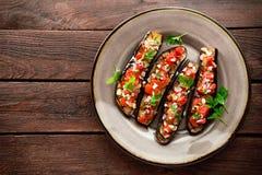 Gebakken aubergines met tomaten, ui en knoflook Gezond vegetarisch voedsel Stock Fotografie
