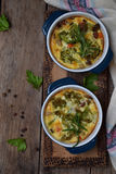 Gebakken braadpan van eieren, bacon, droge tomaten, broccoli en kaas in blauwe ramekin op bruine houten achtergrond Paddestoelgra stock foto's