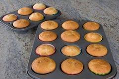 Gebakken cupcakes in pannen Stock Foto's
