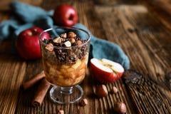 Gebakken die appelstukken met chocoladegranola en hazelnoten worden bedekt stock afbeelding