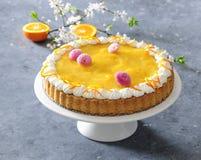Gebakken die biscuitgebak met mandarijnmousse met room en madeliefje eetbare bloemen wordt versierd Royalty-vrije Stock Afbeeldingen