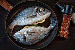 Gebakken Dorado-vissen met groenten in de oven op een donkere achtergrond stock afbeeldingen