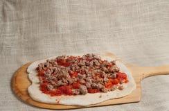 Gebakken eigengemaakte pizza, het uitspreiden organische verpletterde tomaten en hete Italiaanse worst over ontwikkeld deeg 8 Royalty-vrije Stock Foto
