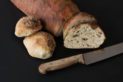 Gebakken enkel zuurdesem eigengemaakte brood en broodjes met zaden - rustieke kwaliteit die met mes door boterhammen liggen Mooie stock afbeelding