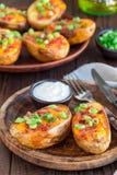 Gebakken geladen aardappelhuiden met cheddarkaas en bacon op houten die plaat, met verticale sjalotten en zure room wordt versier stock afbeelding