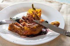 Gebakken kippenbenen met jam en pompoenpuree en bestek stock foto