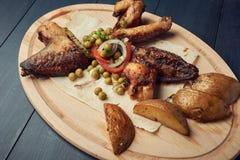 Gebakken kippenvleugels met erwten en ui op houten plaat royalty-vrije stock fotografie