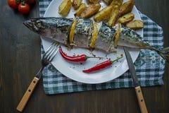 Gebakken makreel met citroen en aardappelen in de schil op een witte plaat Verse product-groenten vegetables Kers, Spaanse peperp royalty-vrije stock afbeeldingen
