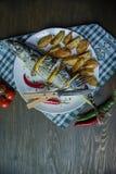 Gebakken makreel met citroen en aardappelen in de schil op een witte plaat Verse product-groenten vegetables Kers, Spaanse peperp royalty-vrije stock foto