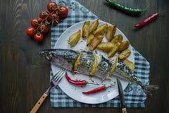 Gebakken makreel met citroen en aardappelen in de schil op een witte plaat Verse product-groenten vegetables Kers, Spaanse peperp royalty-vrije stock afbeelding