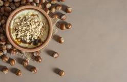 Gebakken rijstebrij Turks melkachtig dessert sutlac in aardewerkbraadpan met hazelnoten stock afbeelding