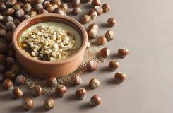 Gebakken rijstebrij Turks melkachtig dessert sutlac in aardewerkbraadpan met hazelnoten stock afbeeldingen