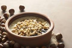 Gebakken rijstebrij Turks melkachtig dessert sutlac in aardewerkbraadpan met hazelnoten stock foto's