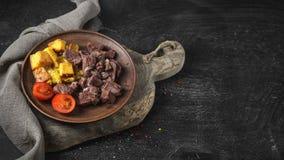 Gebakken rundvlees met croutons, kersentomaten stock afbeelding