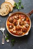 Gebakken varkensvleesvleesballetjes met mozarella en tomatensaus in een pan op een donkere achtergrond stock afbeelding