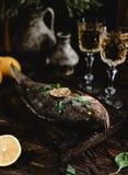 Gebakken vissen met citroen en kruiden op houten raad met witte wijnglazen Royalty-vrije Stock Foto