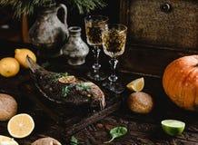 Gebakken vissen met citroen en kruiden op houten raad met witte wijnglazen Stock Foto
