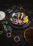 Gebakken zalmlapje vlees met citroen en ui op rustiek metaaldienblad met rijstbijgerecht Royalty-vrije Stock Foto