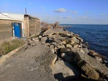 Gebarsten asfalt Vernietigde weg dichtbij het water Grondwaterwas Het concept de vernietiging van wegen van nature Vloed royalty-vrije stock fotografie