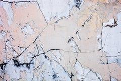 Gebarsten concrete oppervlakte met de overblijfselen van zandig-tanverf Stock Foto