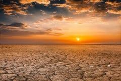 Gebarsten de zonsonderganglandschap van de aardegrond Stock Foto