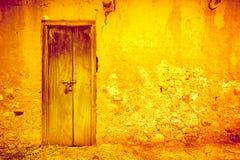 Gebarsten gele muur met deur Uitstekende achtergrond Stock Afbeelding