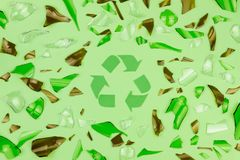 Gebarsten glas op groene achtergrond met groen kringloopsymbool stock foto