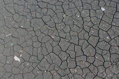 Gebarsten grijze aarde als achtergrond en textuur stock afbeelding