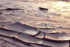 Gebarsten grond bij zonsonderganglicht Stock Afbeelding