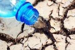 Gebarsten grond met empy fles Stock Foto's