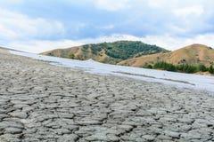 Gebarsten helling met moddervulkaan en bewolkte hemel Droog land in natur Stock Afbeelding