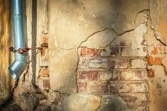 Gebarsten huismuur met het hangen van metaalrioolbuis Royalty-vrije Stock Fotografie