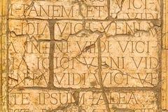 Gebarsten muur met Latijnse inschrijvingen en Roman brieven. stock fotografie