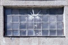 Gebarsten venster na het werpen van stenen en verf stock foto