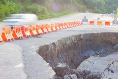 Gebarsten weg na aardbeving met gele barricade Royalty-vrije Stock Afbeelding