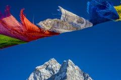 Gebedvlaggen in het Himalayagebergte met Ama Dablam-piek in backgr Stock Foto's