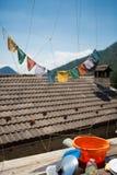 Gebedvlaggen op een dak met een blauwe hemel Stock Afbeeldingen