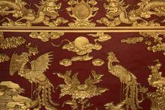 Gebeeldhouwde Phoenix en de draken verfraaien een altaar in een boeddhistische tempel in Hoi An (Vietnam) Stock Fotografie