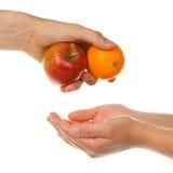 Geben eines Apfels und der Orange Lizenzfreies Stockbild