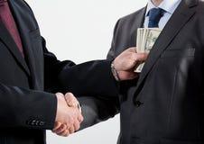 Geben eines Bestechungsgeldes in eine Tasche Stockfotos
