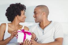 Geben seiner Freundin des gutaussehenden Mannes vorhanden Lizenzfreies Stockbild