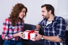 Geben seiner Freundin des jungen Mannes vorhanden Stockbilder