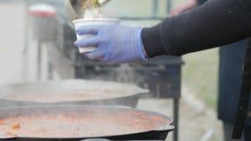 Geben Sie den Flüchtlingen, Freiwillige Mahlzeit vorbereiten das Essen für die des Fliehenkrieges, Lebensmittel für Armen, gießen stock footage