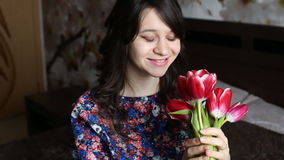 Geben Sie der Frau Blumen, lächelt sie, hebt Blumen auf und überprüft ihr stock footage