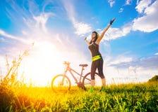 Geben Sie die glückliche Frau frei, die Freiheit auf Fahrrad bei Sonnenuntergang genießt Sportliches Mädchen hob ihre Hände oben  Lizenzfreies Stockfoto