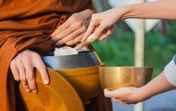 Geben Sie einem buddhistischen Mönch Almosen lizenzfreies stockbild