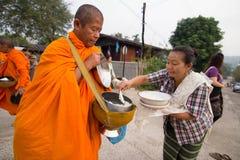Geben Sie einem buddhistischen Mönch am Morgen Lebensmittelangebote Stockbilder